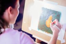 An artist painting a pear.