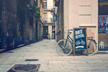 bike rental sign along a sidewalk in Barcelona