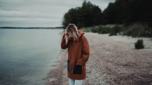 a woman in a jacket walking along a shore