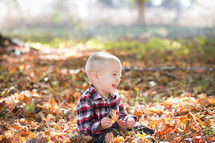 a toddler playing in fall leaves