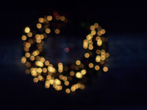 A Christmas wreath decorated with white lights glows in the distant night sky to light up the evening with warmth, cheer and the spirit of Christmas aglow for the holidays.