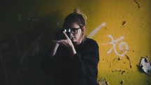 a woman holding a camera standing in front of a graffiti covered wall