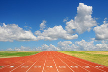 A running track and a blue sky with white puffy clouds.