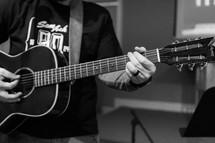 teen boy playing an acoustic guitar