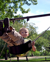 Young boy on a swing in the park.