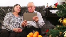 Elderly couple talking on a video call near a Christmas tree