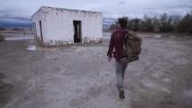 man walking towards an abandoned building