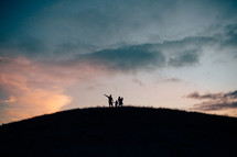 silhouette of a family standing on a hilltop