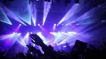 waving raised hands at a concert and stage lights