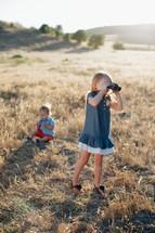 a girl child looking through binoculars