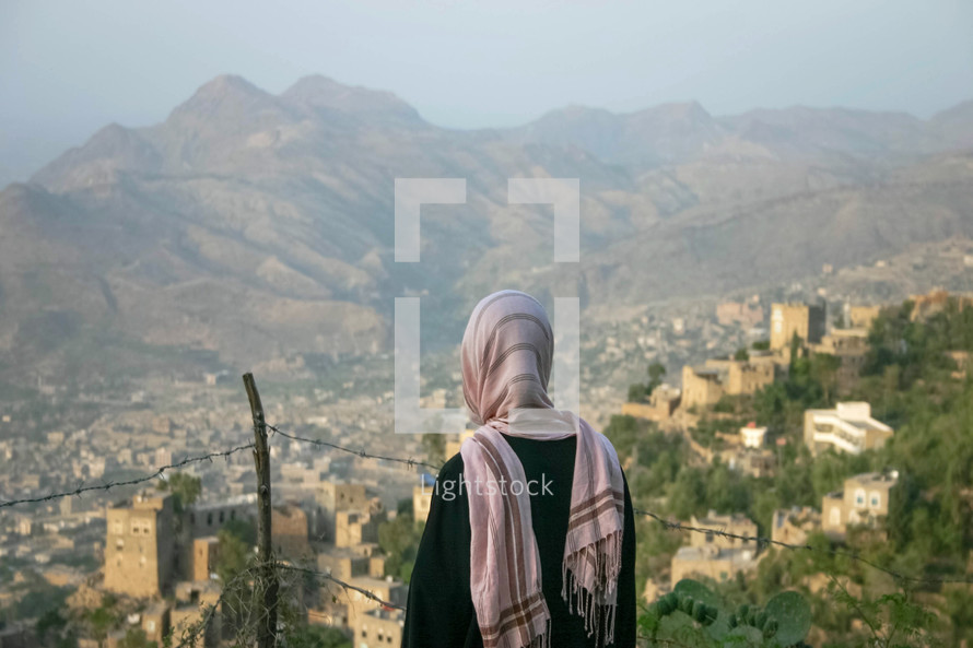 a shrouded woman looking out at a city in Yemen