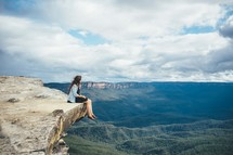 Woman sitting on the edge of a cliff overlooking a valley.