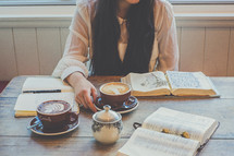 woman drinking cappuccino and reading a Bible