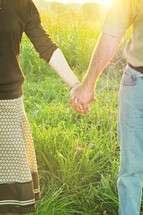 Couple holding hands while standing in tall grass.