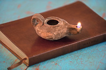 Burning oil lamp pm a Holy Bible.