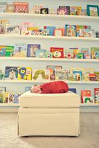 children's books and a newborn on an ottoman