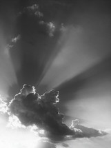 Rays of the sun shining behind a cloud