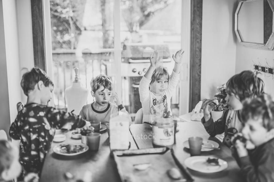 boys sitting at a table having breakfast