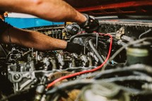 Hands working on a car engine.