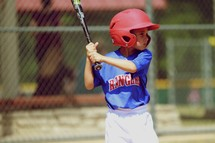 A young boy prepares to swing the bat at a baseball game.