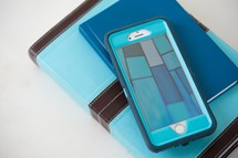 stacked, Bible, journal, and cellphone in teal