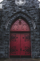 An ornate red door on the front of a stone church.