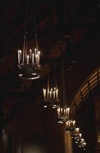 Candelabras hanging from an arched church ceiling.