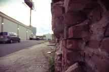 a broken brick wall and sidewalk