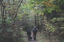 walking through the forest carrying a guitar case