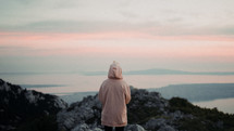 a woman in a hoodie looking out at the ocean view from a mountaintop