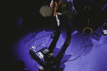 guitarist and foot pedals on stage