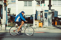 a man on a bicycle riding past a gas station