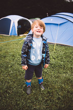 a boy standing in front of tents