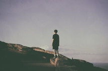a boy standing on a mountaintop