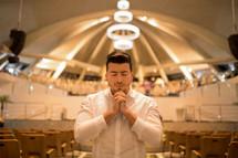 a man in prayer in an empty church