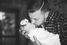 father with a swaddled newborn baby girl