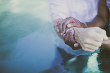 Holding hands during a baptism.