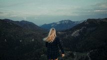 a woman in a plaid shirt looking out at a mountain view