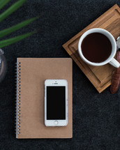 A cell phone on a spiral notebook next to a cup of coffee and wristwatch on a wooden board.