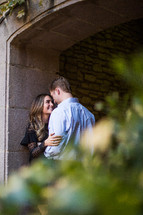 a couple kissing under an archway in a garden