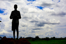 Silhouette of boy standing in field with cloudy sky in the background.