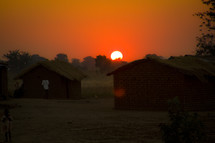 sunset over grass huts