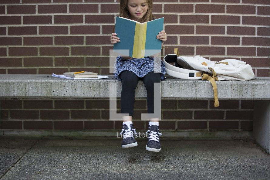 a child sitting on a bench reading while waiting for school