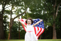 girl child in a white dress holding up an American flag
