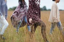 women walking through tall grasses in a field