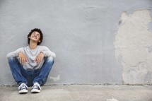 a teen boy sitting and waiting