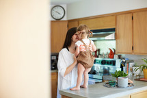 a mother talking to her toddler daughter who is standing on a countertop