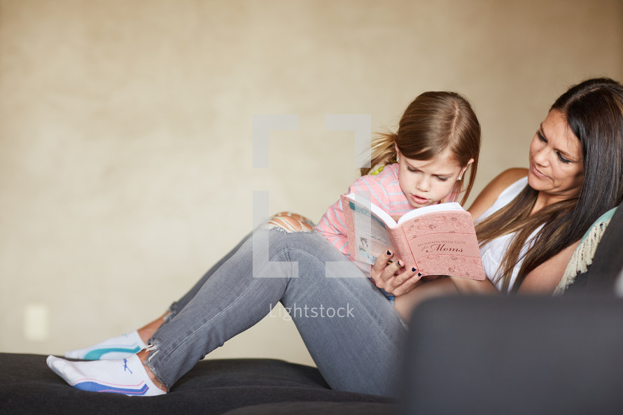 a little girl reading a book to her mom