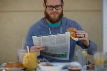 a man reading a newspaper over breakfast