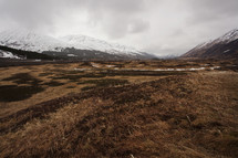 plains in a valley and snow capped mountains